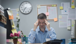 Office-Worker-With-Headache-75399391