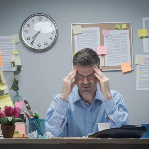 Office-Worker-With-Headache-75399391