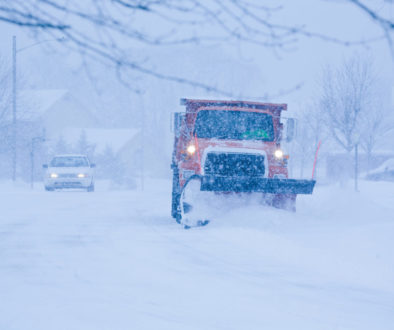 Heavy snowfall and a car behind the snowplow